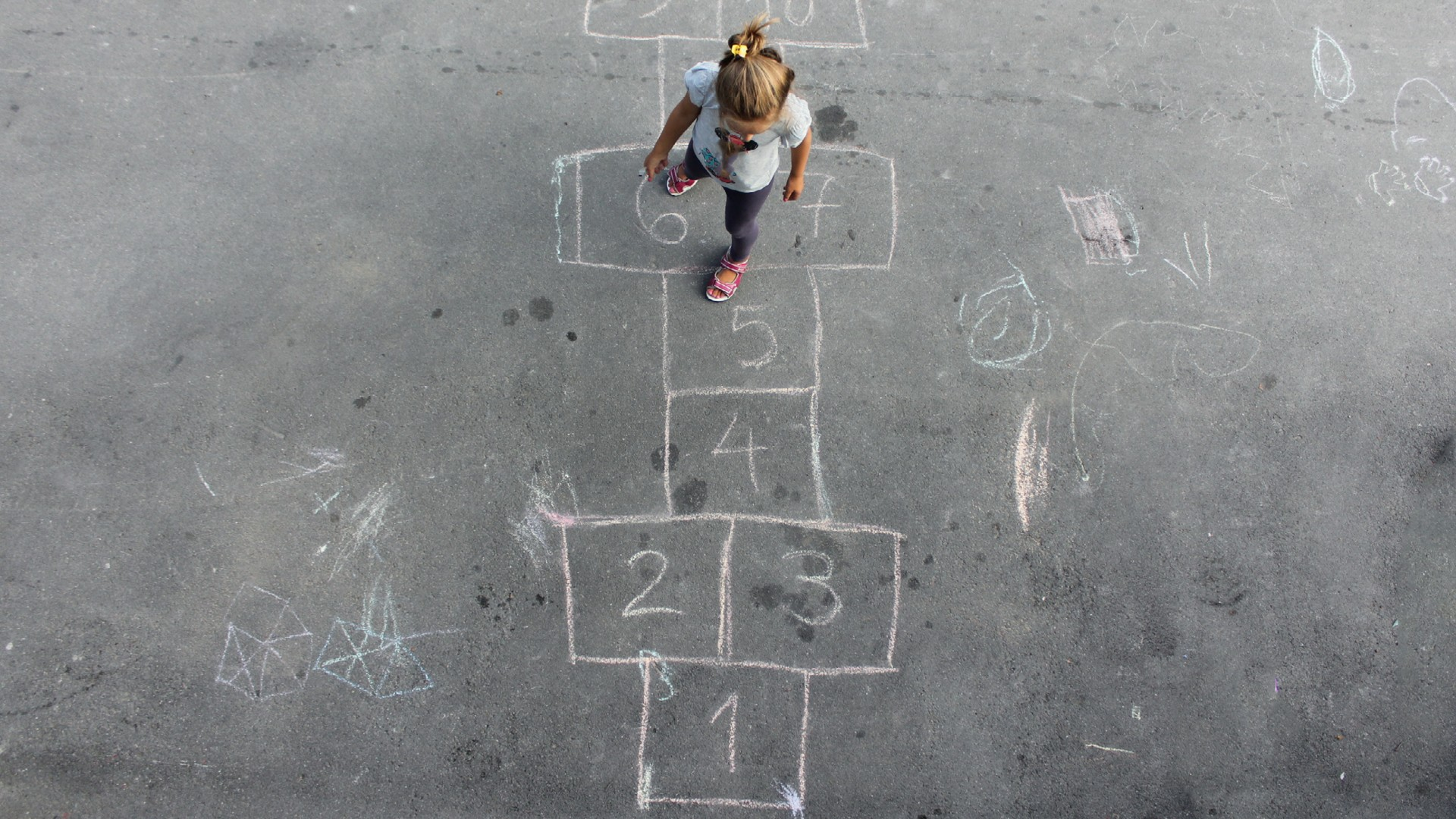 Bambina che gioca in strada al gioco della Campana